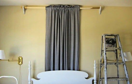 Hanging the drapes to set up the bed canopy