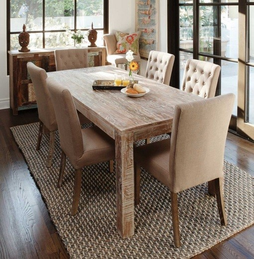 Distressed wood dining table with tufted chairs on brown rug
