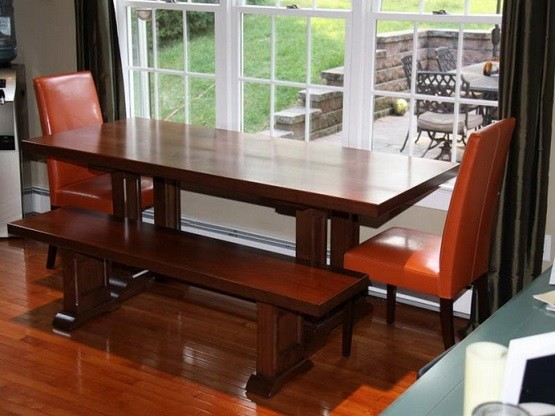 Wooden narrow dining room table and brown chairs